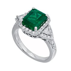 RE26422: This outstanding emerald ring possesses a 3.00ct center stone set in 18K white gold with 0.47ct premium cut round diamonds and 0.24ct trillion cut diamonds.