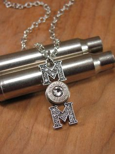 """From our new """"GUNZ & GLITZ™"""" value priced collection, we offer this sparkly """"MOM"""" sterling plated pendant. Glass crystals are encrusted in both of the """"M""""s and the center bezel for the """"O"""" is the perfect size to nestle a 38 special or 40 S&W casing. We only use major brands of casings and will set the bezel with either a 38 special or 40 S&W. You choose either brass or nickel casing. Comes with or without a diamond Swarovski crystal in the center of the bullet casing. Use the ..."""