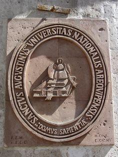 Cacería Tipográfica N° 215: Otro escudo de la Universidad San Agustín tallado en sillar rojo en el primer patio de la casona ubicada en la calle del mismo nombre en el Centro Histórico de Arequipa.