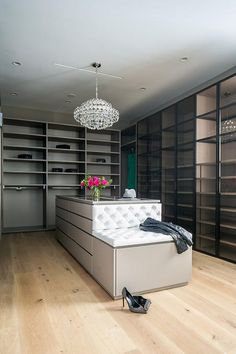 Luxurious walk-in closet is lit by an Aerin Sanger Chandelier hung over a gray island fitted with flat front cabinets and a custom gray bench finished with white tufted cushions. Built In Dresser, Built In Bench, Tiffany Harris, Dream Home Design, House Design, Closet Chandelier, Bedroom Built In Wardrobe, Closet Island, Dressing Room Closet