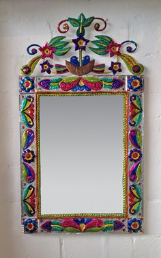 Love the home made Mexican feel of this bright mirror. -Large Mexican hand worked tin framed wall mirror. Crafted floral design topped with doves.