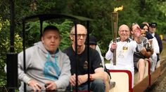 Torchbearer Paul Freedman MBE carries the Olympic Flame whilst riding the miniature railway in Barking Park on the Torch Relay journey between Redbridgeand Barking and Dagenham.