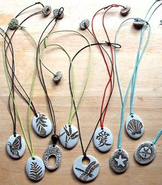 Handmade Porcelain pendant designs strung up onto colored cotton cord and finished with a handmade porcelain bead for the clasp
