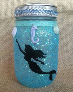 This beautiful light is made with a pint size mason jar covered in 2 layers of glitter and sealed to prevent the glitter from falling off. A mermaid silhouette is added to create a gorgeous light perf Mason Jar Crafts, Mason Jar Diy, Bottle Crafts, Mermaid Crafts, Mermaid Diy, Disney Diy Crafts, Mermaid Room, Fairy Jars, Painted Jars
