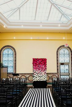 Brides.com: . A bold black-and-white aisle runner leads up to a spectacular hedge of flowers in an ombré gradient of poppy reds, pinks, and white. Florist Linnea Asiel drew inspiration for the design from the bride's love of all things Kate Spade.