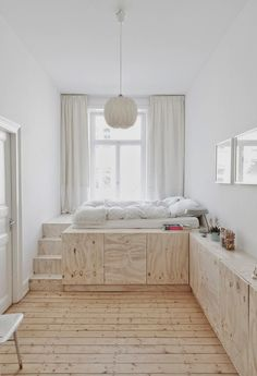 Studio Oinks solution for a small, high-ceilinged room is to create storage under an elevated bed platform.
