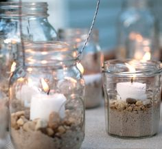 Light up your summer night with beach jar candle holders. A mismatched group of mason jars sits atop a table. Fill your jars with sand, add some mini shells and/or small beach pebbles, place a candle on top, then sit back and enjoy. Mason Jars, Mason Jar Crafts, Glass Jars, Candle Jars, Candle Holders, Beach Jar, Decorated Jars, Beach Crafts, Beach Themes