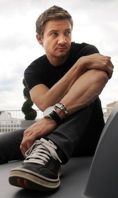Jeremy Sitting on a Bench Wearing a Black T-Shirt and Pants and Sneakers With Watch and Bracelet on Left Wrist
