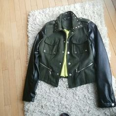 Jacket Olive green material with black faux leather sleeves. Has two breast pockets and two zipper pockets on the front, a studded collar. And silver snap buttons. The sleeves also have zippers and snaps. Never worn. Jackets & Coats