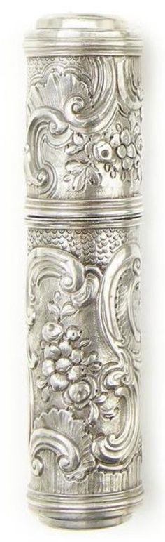 An embossed silver spy-glass nécessaire, English, late 18th century, with embossed flower and C-scroll decoration, sliding covers to eyepiece and objective, opening to fitted interior with folding scissors, ivory note leaf, tweezers, penknife, ear scoop and pencil, 4 1/4in (11cm) long