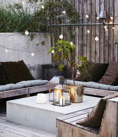 guirlande lumineuse exterieur au dessus d un salon de jardin en bois, constitué de bancs en bois et table en béton, revetement sol bois, amenagement terrasse exterieure
