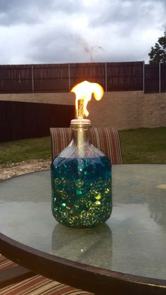 DIY Tiki Torch! I placed beads in the bottle of an apple cider bottle, screwed a hole in the metal cap, inserted the wick and filled with Tiki torch fluid! We love the table top tiki!