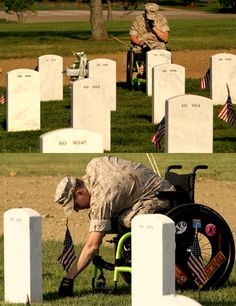 Marine Lance Cpl. Brandon Long, who was injured losing both legs while serving in Afghanistan, mourns at Arlington National Cemetery as American flags are placed in front of each headstone in preparation for Memorial Day, in Arlington, Virginia, on Thursday, May 26, 2011. (AP Photo/Jacquelyn Martin)
