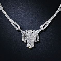A classic and dressy 1930s vintage diamond necklace culminating in a sparkling central tassel composed of 25 sizable baguette diamonds. The center section is suspended from looped diamond-set terminals completed by a line of round brilliants, each side punctuated by a jauntily stepped panel of baguettes. Both stunning and sophisticated and fun and flirty. 12.00 carats total diamond weight; 17 inches not including the tassel.