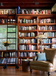 Love little home libraries like this. The bookshelf design makes the room so warm and organized!