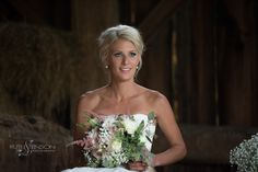 The bride sits on top of bales of hay in an old barn posing and smiling and looking positively radiant