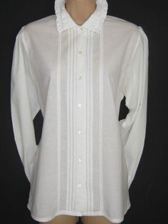 L A U R A A S H L E Y  I dont like ephemeral things, I like things that last forever  A TRADITIONAL VINTAGE LAURA ASHLEY WHITE SHIRT BLOUSE IN THE BEAUTIFUL 100% SOFT COTTON FABRIC.  THE COLLARED NECKLINE FEATURES A DOUBLE ROW OF RUFFLE TRIM AND MAY BE WORN IN HIGH NECK STYLE. VERTICAL PIN TUCKS DECORATE EACH SIDE OF THE FRONT BUTTON FASTENING DOWN TO THE LOVELY LONG HIP-LENGTH HEM. SLEEVES PLEAT AT SHOULDERS, ENDING IN ONE-BUTTON FASTENING RUFFLE CUFFS.  A MOST BEAUTIFUL BLOUSE TO COMBINE…