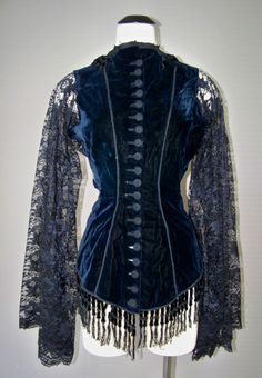 Circa 1890s back view of a blue velvet dress bodice, decorative buttons, and trimmed with beading. Sleeves are delicate lace, tight at the wrists.