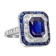 Sapphire and diamond panel ring, centering on a cut-cornered, rectangular-cut sapphire weighing 4.85 carats, within a baguette-cut diamond surround trimmed with calibre-cut sapphires, the shoulders set with baguette-cut diamonds, mounted in platinum. Comes with certificate from the Gubelin Laboratory, number 9403081, stating that the sapphire is natural and of Burmese origin. 20th century