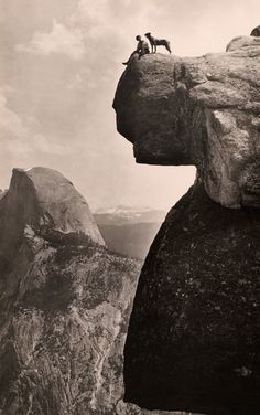A man and his dog on the Overhanging Rock in Yosemite National Park, May 1924. Photograph by Educational-Bruce Photograph.