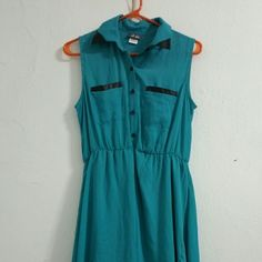 Dots High-low Button Down Sleeveless Dress High-low sleeveless dress with button down collar top from Dots. Size medium. Teal color with black faux leather trim on chest pockets and collar. Soft skirt lining. Polyester material. Never worn. NWT. Dots Dresses High Low