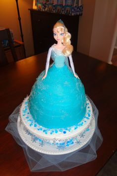 "Elsa Disney Frozen Dress Cake.  It uses two cakes (a round cake pan on the bottom and the Wilton Dress Cake pan on top).  I sprinkled the frosting (right away while still moist) with sanding sugar for sparkle.  The ""Frozen Fractals"" around her are sugar pieces from Wilton (found at Walmart)."