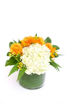 White hydrangea and orange dahlias are the stars of this modern, polished design in a leaf-wrapped vase. From Eight Tree Street via Bloompop