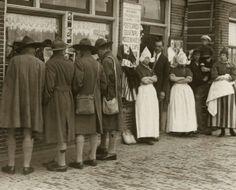 Padvinderij, scouting. Engelse verkenners op bezoek in Volendam bekijken een etalage van een souvenirwinkel. Voor de winkel mensen in Volendammer klederdracht. Nederland, Volendam, 1926.