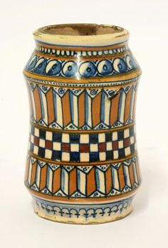 A copper lustre Albarello, probably 16th century and Faenza, with a central chequerboard band between ochre zigzag and wrigglework borders, chips and glaze loss, 13cm