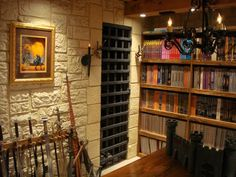 The Burntwire Brothers remodeled a room to house their collection of D paraphernalia as well as a place to hold game sessions. There are stained glass windows, faux dungeon walls, a metal portcullis, dragon statuettes and a rack of swords