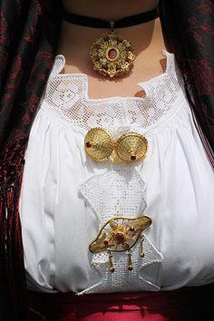 I gioielli che accompagnano la tipica camicia del costume sardo.