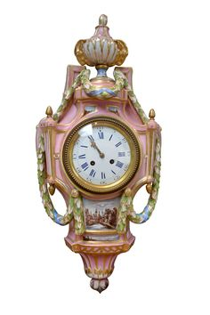 Louis XVI Style Pink Porcelain Cartel Clock - Late 19thC  Porcelain cartel clock in the Louis XVI style; the predominantly pink case surmounted by a classical urn with goats heads and colored enamel swags; below the white enamel dial with Roman numerals is a well painted village scene; Meissen mark in under glaze blue; eight day French movement ringing the half hour and hours; French/German late 19thC