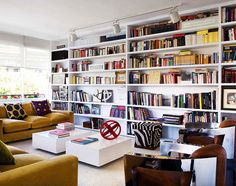 I could fall in love with this room - simple lines, white, splash of color, and room for so many books books books!