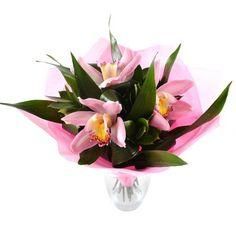 Трепетные лепестки орхидей цвета туманно-молочной зари горят искорками нежности и симпатии, словно кувшинки на темных водах тихого озера. Зелень аспидистры прекрасно справляется с ролью прохладной речной глади и эффектно подчеркивает хрупкость цветов.