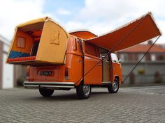 Amescador camper with an extention and awning. And bright orange.
