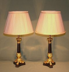 A pair of mid Century bronze & ormolu Candlesticks having leaf nozzles above tapered black marble stems raised on acanthus leaf scrolled legs ending on concave triform bases. (Now converted to lamps.) Ref: 5383 Circa: 1840 Candlestick Lamps, Candlesticks, Lantern Chandelier, Lanterns, Acanthus, Concave, Black Marble, Stems, Antique Furniture