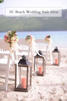 wooden lanterns with coral pillar candles lining the aisle