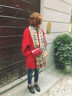 Un paio di scarpe stringate da donna e un ampio cappotto rosso accesso, in pendant con la piccola tracolla, rendono particolare questo look.