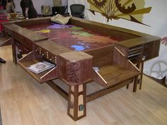 """The Sultan Gaming Table: Flip down """"personal"""" player station desks with secret drawers and """"rail system"""", Cup holders, Hardwood Dice Towers and humorous descriptions to boot! If only I had the Space"""