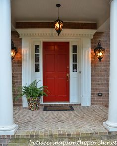 A red front door stands out from the brick of this traditional home