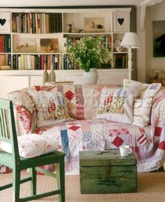 Cottage charm living room - love the quilt on the sofa and the heart doors on the bookcase
