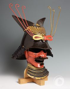 """Kawari kabuto Mid Edo period (1615-1867) 18th Century """"Spectacular"""" samurai helmet shaped with a fantastic form. Iron, harikake and parcel-gilt. This unrecorded shape does not seem to resemble any natural shape, if not maybe a large kuwagatamaedate, a decoration for helmets used in the medieval armors. Harikake had been used during the Momoyama period (1573-1715), when generals begun to wear large helmets which had to be light at the same time."""