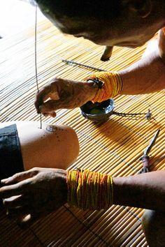 Tattoo in Mentawai: A sipatiti (Mentawai's tattoo artist) draws a simple tattoo design using a sharp palm leaf's splin...