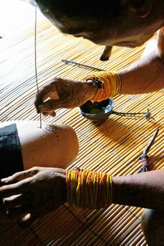 Tattoo in Mentawai: A sipatiti (Mentawai's tattoo artist) draws a simple tattoo design using a sharp palm leaf's splin...