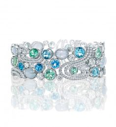 A spectacular, colourful bangle from Boodles, featuring 13.71ct of green tourmalines, 6.22ct of aquamarines, 5.53ct of moonstones, 5.33ct of cabochon sapphires, 5.47ct of blue topaz and 4.92ct of round-brilliant cut diamonds in platinum.
