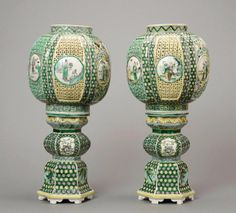 A pair of Chinese famille-verte lanterns, Qing Dynasty, 19th century in coloured enamels on the biscuit, each lantern pierced and moulded into 6 vertical sections, each one with figures in a round medallion; supported on a waisted pedestal on six shaped feet 39.7cm high