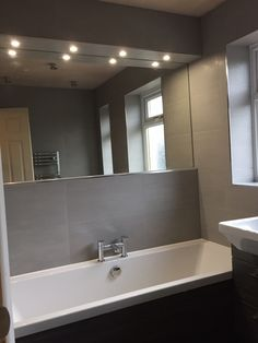 Bathroomdesigned With Mirror And Lighting Above Bath