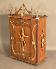 a wood wall cabinet with antler decorations