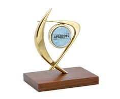 Troféu personalizado com logomarca evidenciada Peça: bidimensional, 17 cm de altura. Materiais disponíveis: alumínio (prata) ou bronze (dourado ou patinado). Base: madeira natural ipê ou madeira revestida de fórmica preta, 14x9x2cm. Placa cortesia: aço inox (prata) ou latão (dourada), 6x2cm, placa central 5 cm de diâmetro.