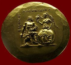 """gold medallion of Alexander the Great: Greek, Macedonia, 218-246 CE Nike hands helmet to Alexander; the shield she holds shows a Greek warrior defeating an Amazon, similar to a figure on Pheidias' statue of Athena Parthenos. The inscription, in Greek, reads """"Alexander, the King."""" Berlin, Pergamon Museum. Credits: Barbara McManus, 2005 Keywords: coin, Hellenistic empire"""